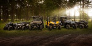 A line of Can-Am offroad vehicles in a forest